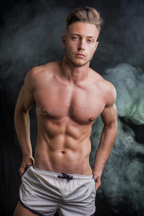 Lean athletic shirtless young man standing on dark background royalty free stock photography