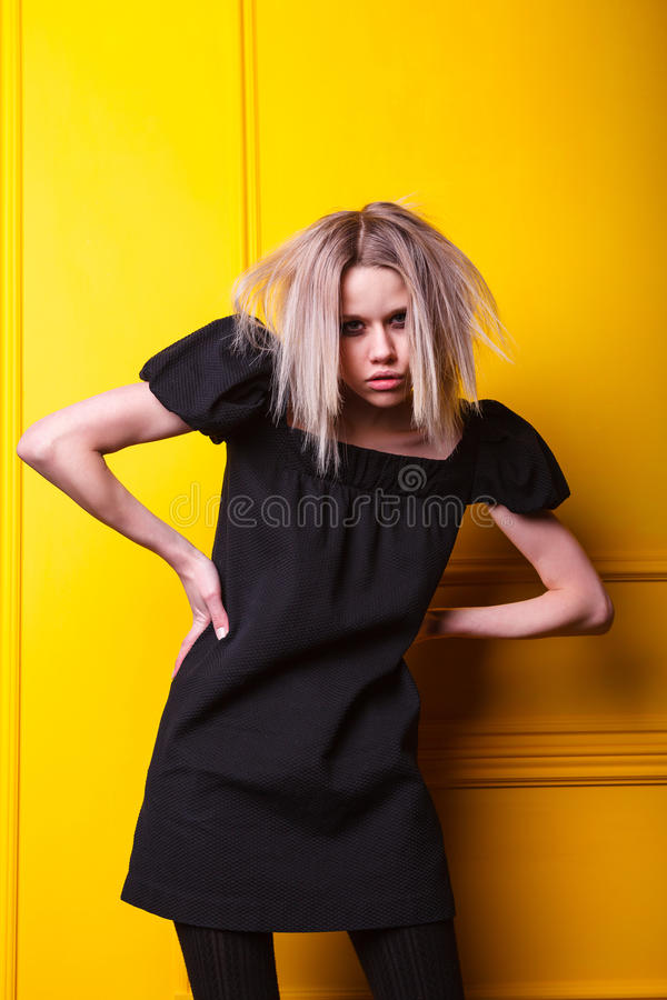 Lean girl posing on yellow background royalty free stock photo