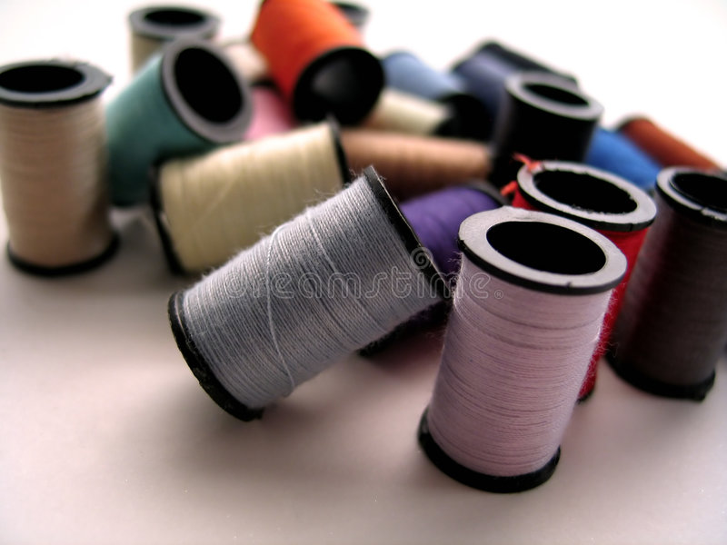 Lean on Me. Blue thread spool resting against a pink thread spool. A bunch of multi-colored spools out of focus in the background royalty free stock photo