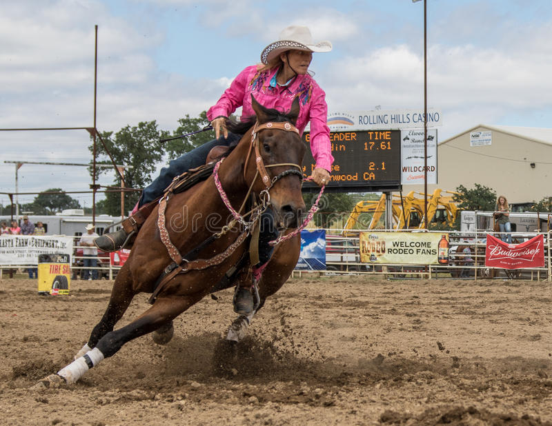 Leaning into the Corner. A cowgirl clears a barrel during a barrel racing event. The rodeo in Cottonwood, California is a popular event on Mother's Day weekend stock image
