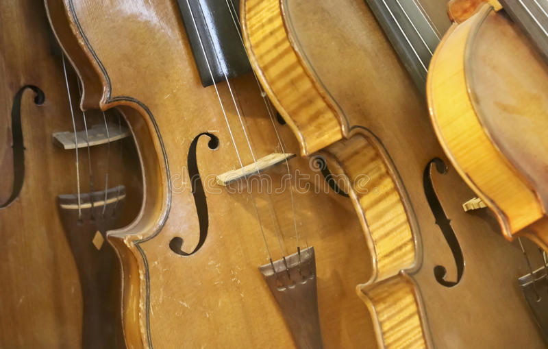 A Leaning Stack of Vintage Antique Violins. Or Fiddles stock photo