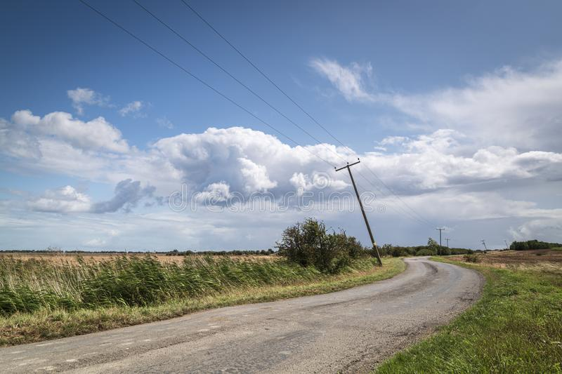 Leaning Telegraph Poles. A road with leaning telegraph poles winding through the Isle of Sheppy countryside towards Harty Ferry, Kent, England stock images
