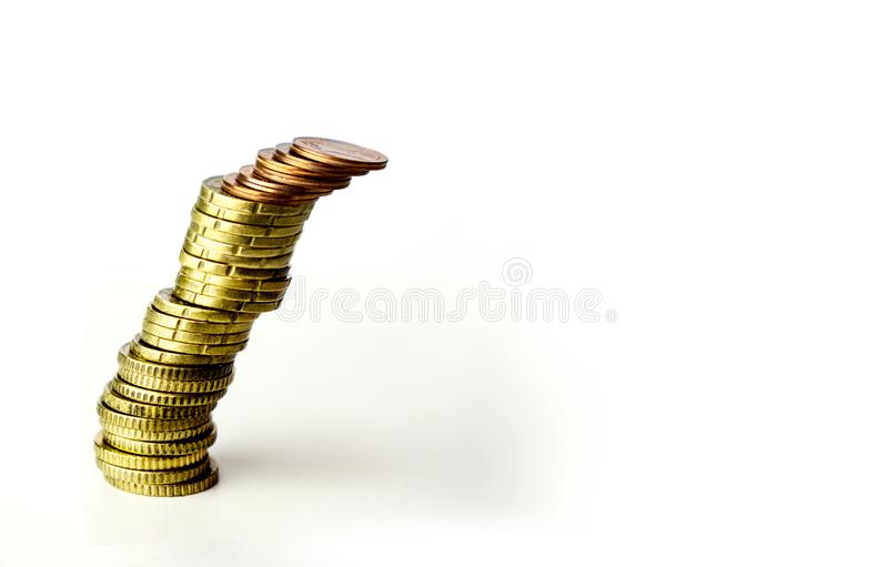 Leaning tilt stack of coins on white background - risky business concept stock photography