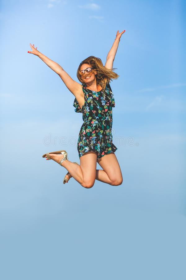 Leap of happiness. Joyful and smiling young woman jumps up with arms raised stock photo