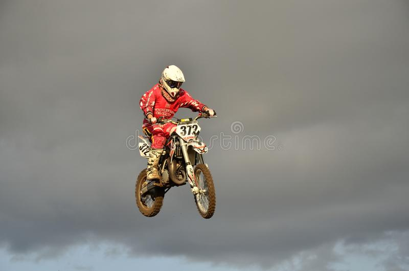 A leap over the hill, motorcycle racer royalty free stock photo