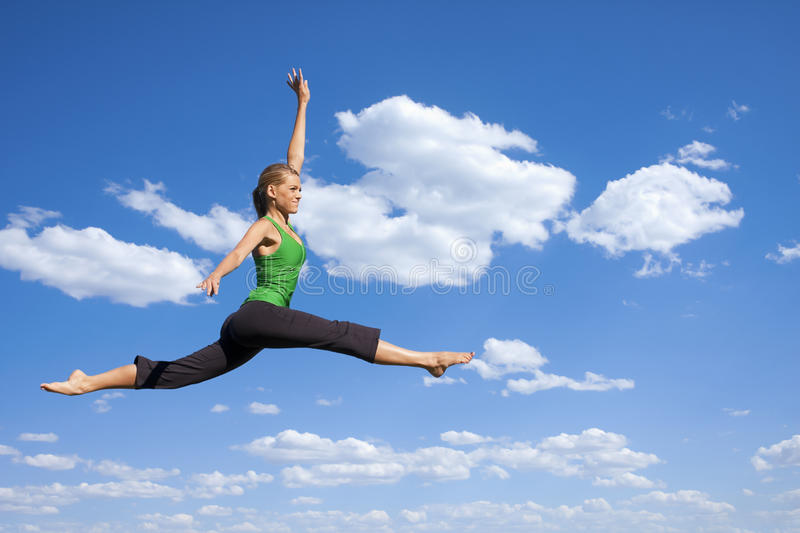 Leaping and Dancing Woman. A beautiful woman gracefully jumps in the air stock photography