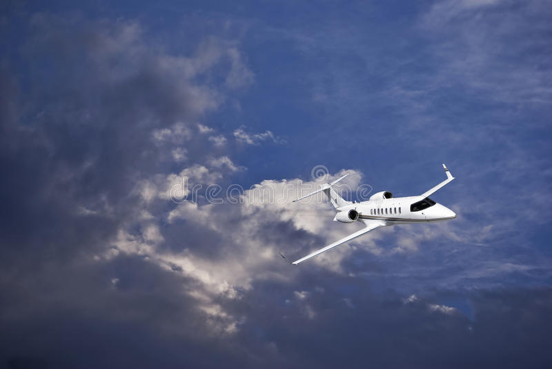 Learjet 45 with Blue Sky & Storm Clouds. Business jet (Learjet 45) zipping through the skies, with storm building in the clouds in the background. [Special stock photography