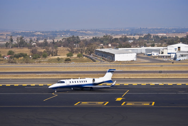 Learjet 45 - Business Jet. Learjet 45 parked in the middle of the apron. Also visible in the background is the flat, wide open landscape. FALA — Lanseria stock photos