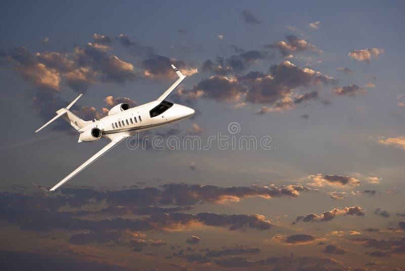 Learjet 45 con las nubes de la puesta del sol fotografía de archivo libre de regalías