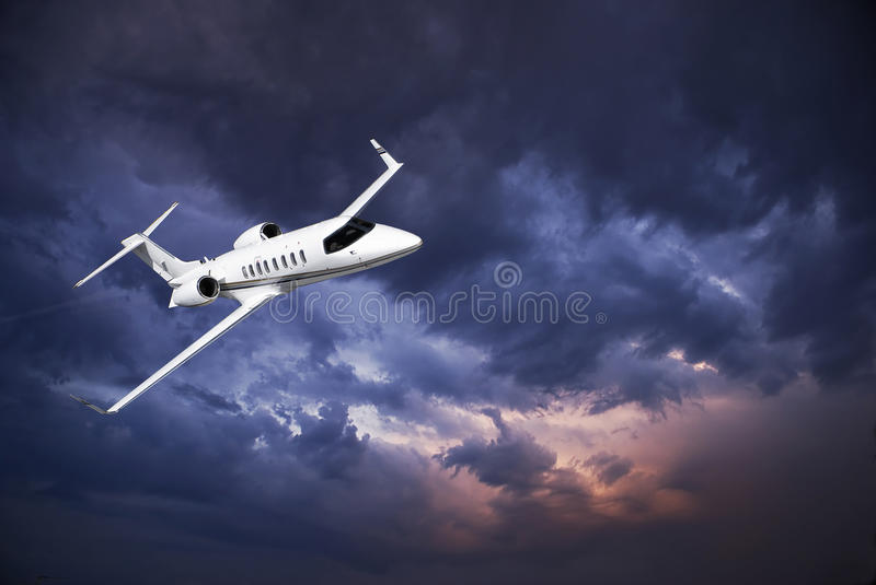 Learjet 45 with Storm Clouds. Business jet (Learjet 45) zipping through the skies, with storm building in the clouds in the background. [Special thanks to John stock images