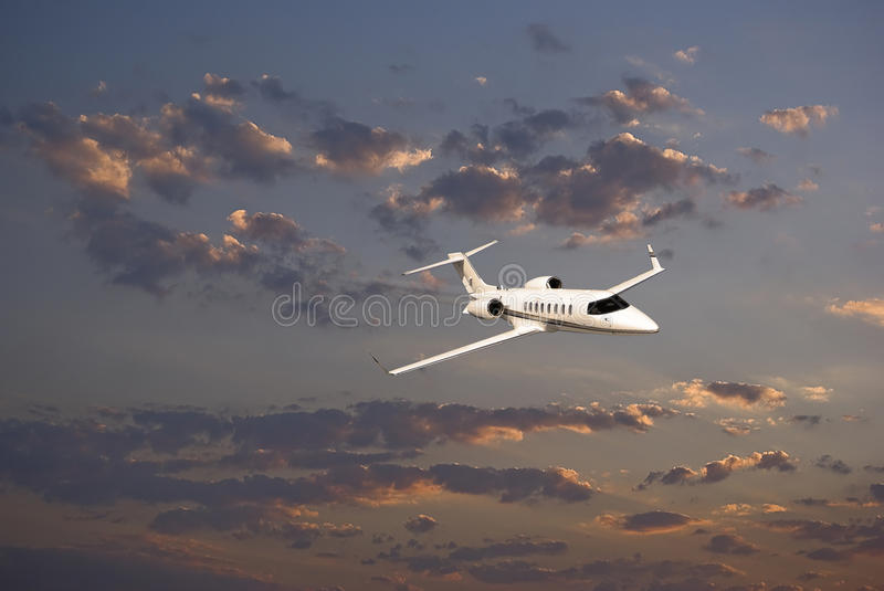 Learjet 45 with Sunset Clouds. Business jet (Learjet 45) zipping through the skies, with sunset bouncing off the clouds in the background. [Special thanks to stock image