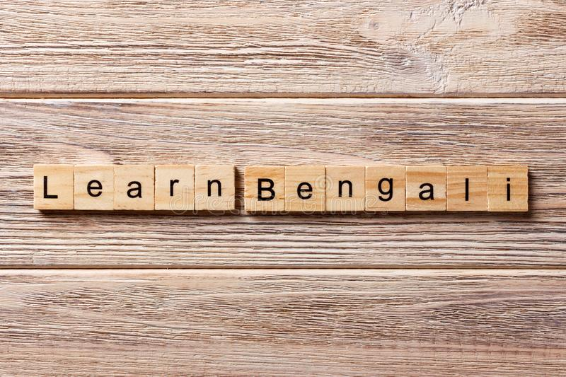 Learn Bengali word written on wood block. learn Bengali text on table, concept.  royalty free stock photo