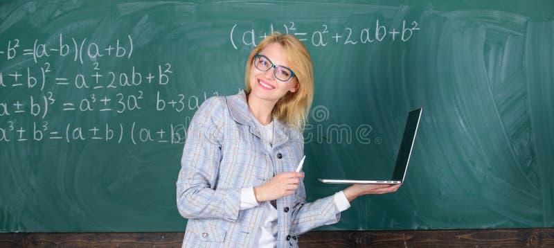 Learn it easy way. Woman teacher wear eyeglasses holds laptop surfing internet. Educator smart clever lady with modern. Laptop surfing internet chalkboard stock image