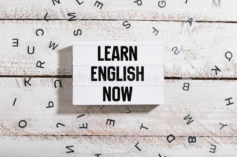 Learn English now in light box on white wood desk. Learn English now message written in light box on white table desk flat lay royalty free stock photography