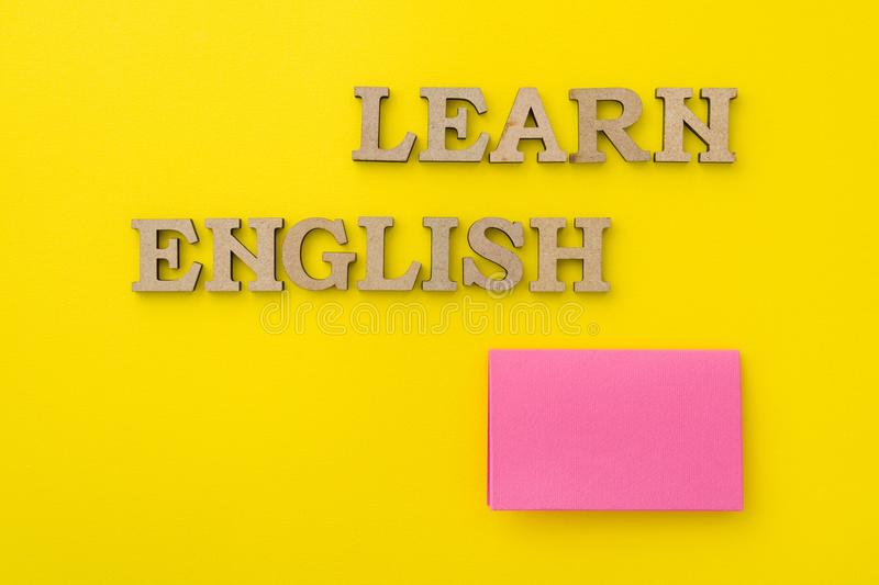 Learn English, words in wooden letters with yellow background. royalty free stock photography
