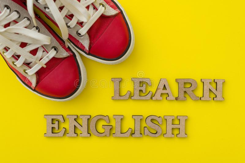 Learn English, words in wooden letters with yellow background in front of red youth sneakers royalty free stock photography
