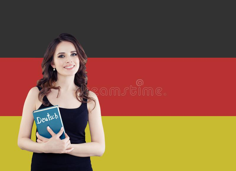 Learn German language. Attractive young woman holding phrasebook against the Germany flag background royalty free stock photography