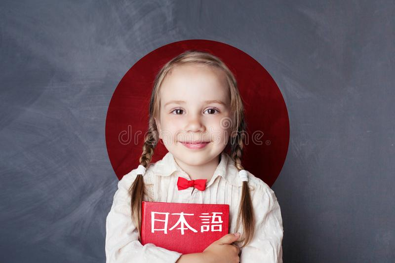 Learn japanese language. Smiling kid pupil on Japan flag stock photo