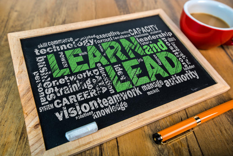 Learn and lead word cloud. On small blackboard royalty free stock photography