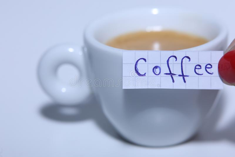 Coffee word written on a small note. Learn new language, Coffee word written on a small math note. White background, copy-space stock photos