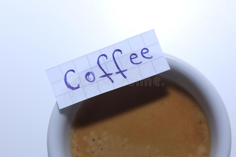 Coffee word written on a small note. Learn new language, Coffee word written on a small math note. White background, copy-space stock photo
