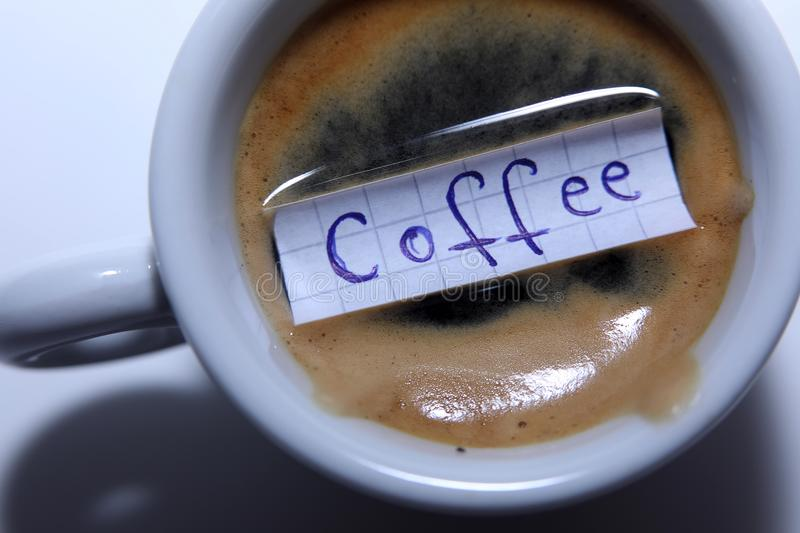 Coffee word written on a small note. Learn new language, Coffee word written on a small math note. White background, copy-space royalty free stock images