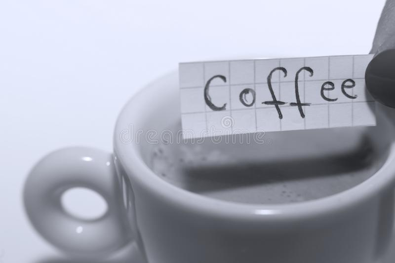 Coffee word written on a small note. Learn new language, Coffee word written on a small math note. White background, copy-space stock images