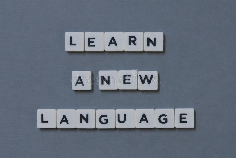 ' Learn A New Language ' word made of square letter word on grey background royalty free stock photo
