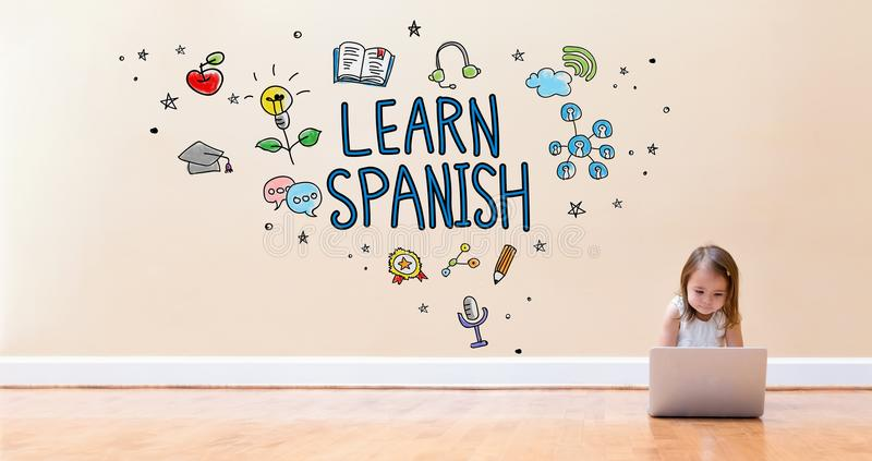 Learn Spanish text with little girl using a laptop computer stock photos