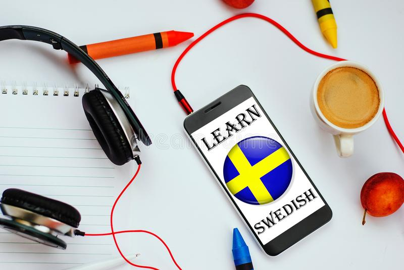 Learn Swedish concept. Smartphone with Swedish flag and headphones. concept of swedish learning through audio courses royalty free stock image