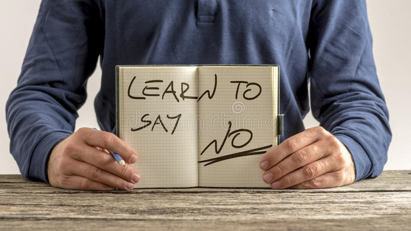 Learn to say no. Front view of a man showing an open note pad with a handwritten message - Learn to say no royalty free stock photography