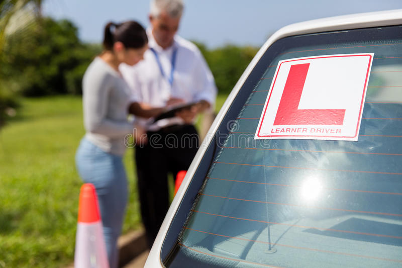 Learner driver sign car. Learner driver sign on a car with student and instructor standing behind stock photos