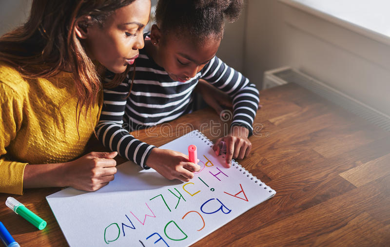 Learning the alphabet. At home with her mom, black mother and child royalty free stock image