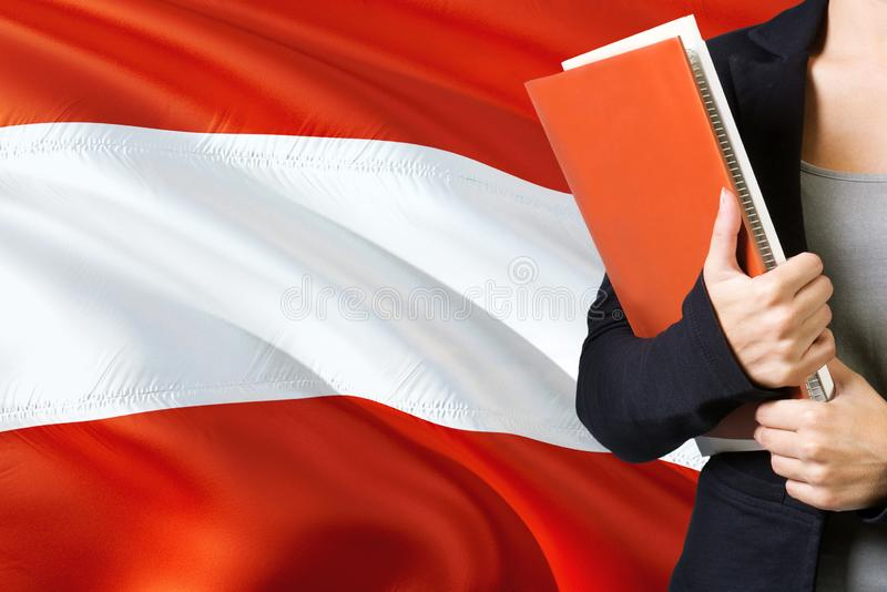 Learning Austrian language concept. Young woman standing with the Austria flag in the background. Teacher holding books, orange royalty free stock photography