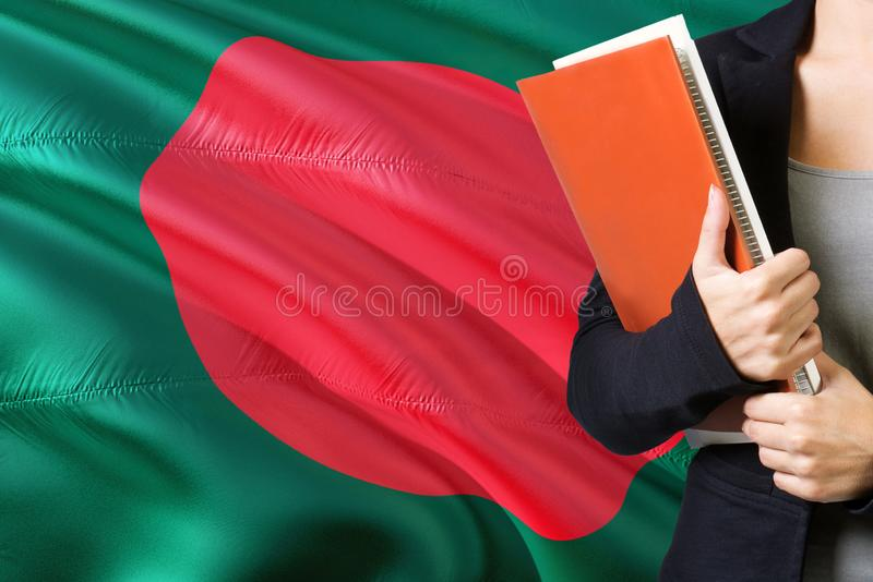 Learning Bangladeshi language concept. Young woman standing with the Bangladesh flag in the background. Teacher holding books, stock image