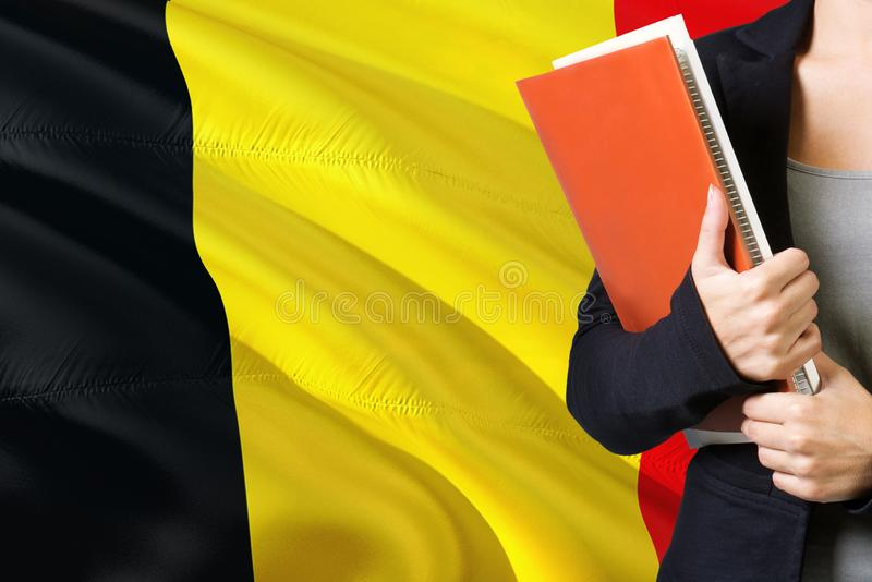 Learning Belgian language concept. Young woman standing with the Belgium flag in the background. Teacher holding books, orange royalty free stock images