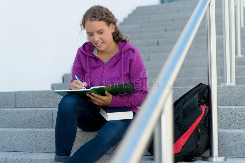 Learning blond female student at stairs royalty free stock photo