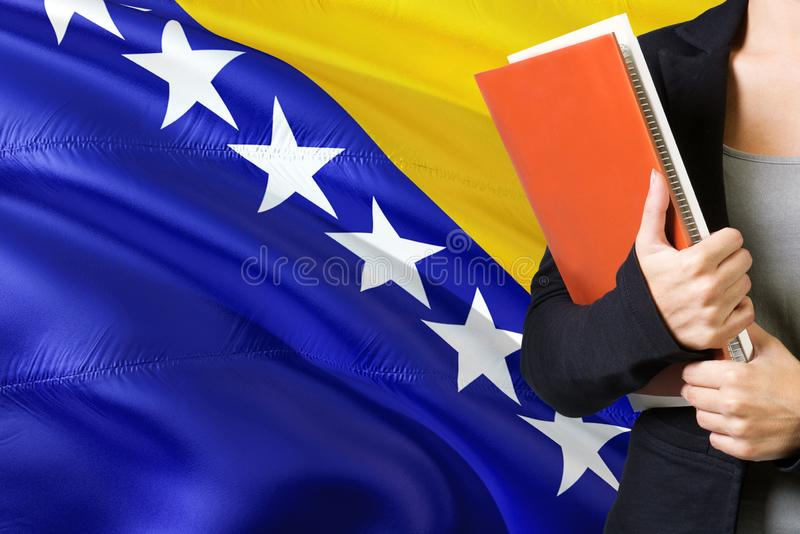 Learning Bosnian language concept. Young woman standing with the Bosnia Herzegovina flag in the background. Teacher holding books. Orange blank book cover royalty free stock photos