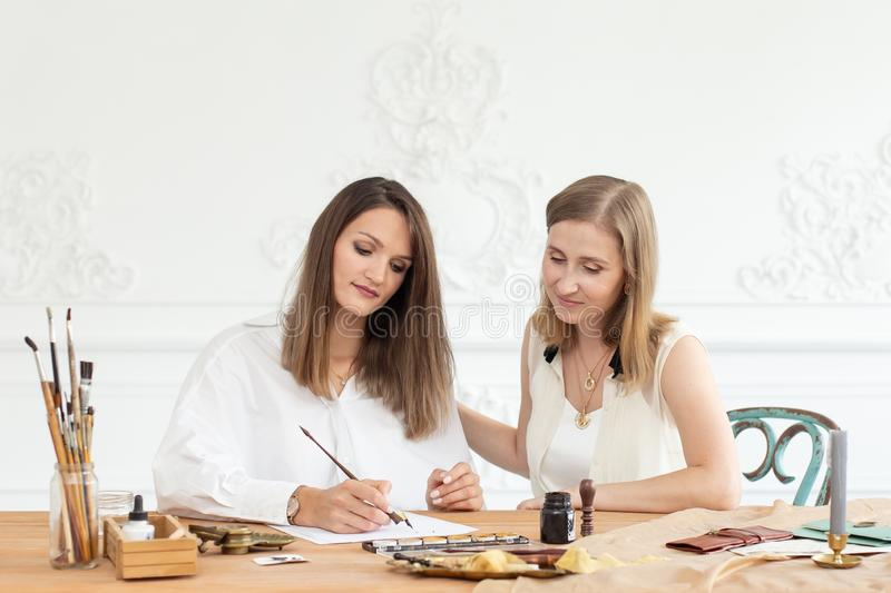 Learning calligraphy in art workshop. Teacher and students. Art school handwriting. stock photography
