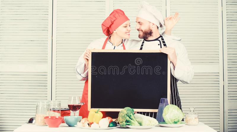 Learning classic techniques for dishes. Couple of man and woman gesturing ok at board in cooking school. Chef and cook stock photo