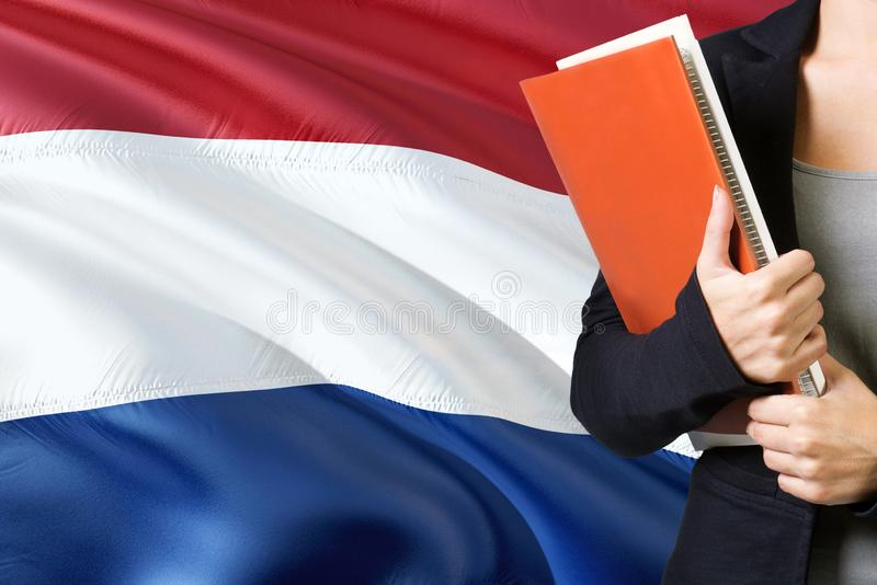 Learning Dutch language concept. Young woman standing with the Netherlands flag in the background. Teacher holding books, orange stock image