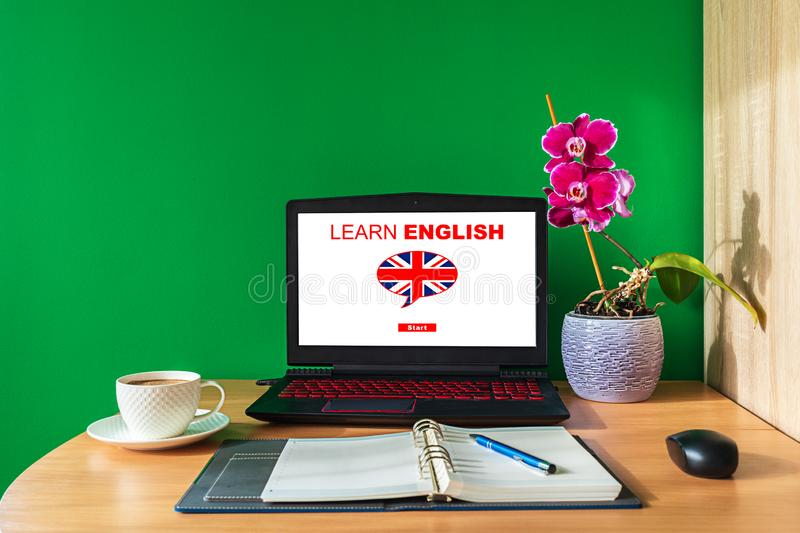 Learning English online concept using computer. Laptop screen displaying english lessons poster with British flag. Closeup of stock photos