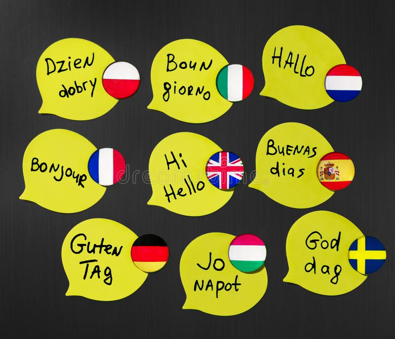 Learning foreign languages ​​courses. Phrase greetings in different languages. Flags of the countries of the studied languages stock photo