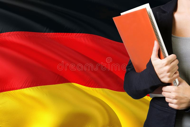 Learning German language concept. Young woman standing with the Germany flag in the background. Teacher holding books, orange royalty free stock images