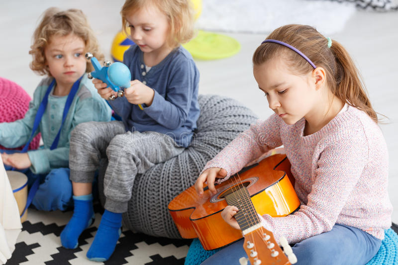 Learning how to play. Cute girl learning how to play the guitar in kindergarten stock images