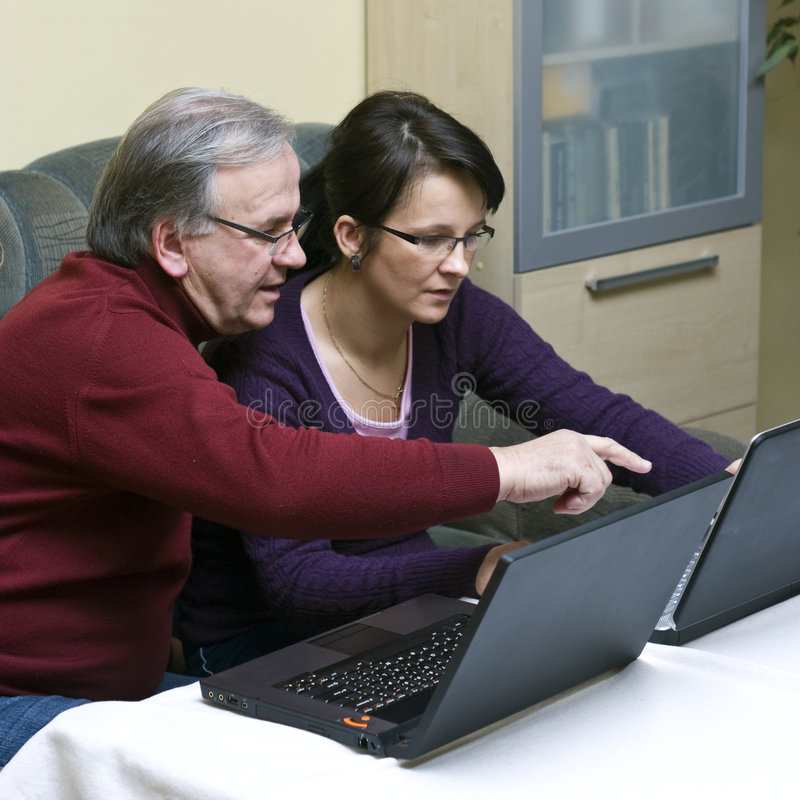 Learning how to use laptop. A woman (daughter) teaching a senior man (father) how to use a laptop. Square format photo royalty free stock image