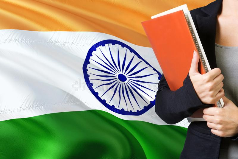 Learning Indian language concept. Young woman standing with the India flag in the background. Teacher holding books, orange blank stock photos