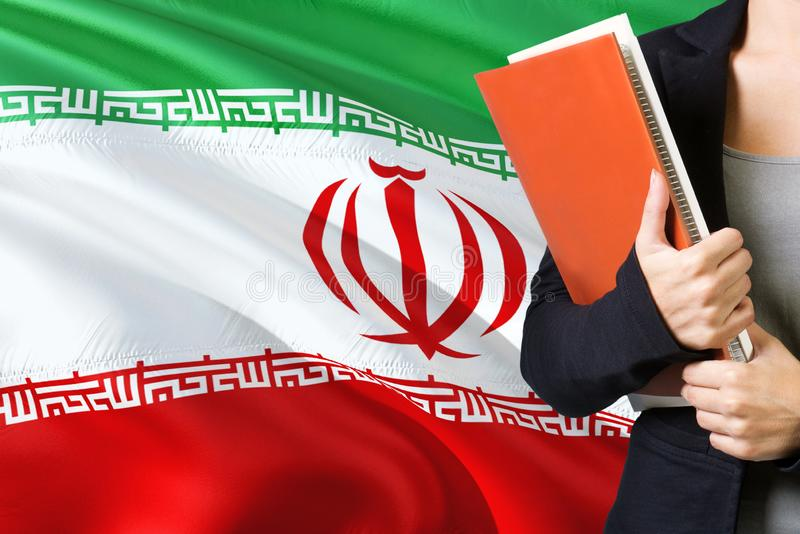 Learning Iranian language concept. Young woman standing with the Iran flag in the background. Teacher holding books, orange blank stock images