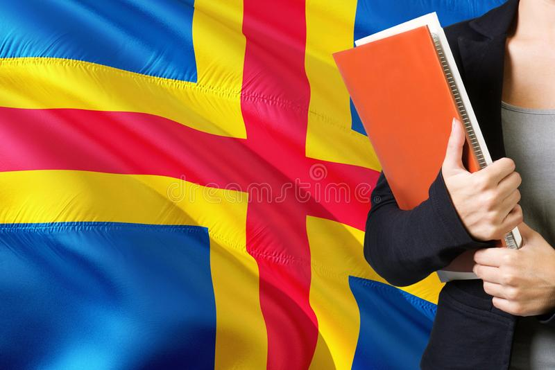 Learning language concept. Young woman standing with the Aland Islands flag in the background. Teacher holding books, orange blank. Book cover stock images