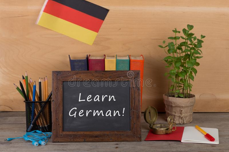 "Learning languages concept - blackboard with text ""Learn German"", flag of the Germany, books, chancellery. On table and wooden background stock image"
